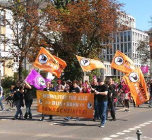 """Piraten auf einer Demonstration mit Fahnen der Piratenpartei und einem Transparent mit der Aufschrift """"Mobilität für Alle - Bus und Bahn Fahrscheinfrei"""