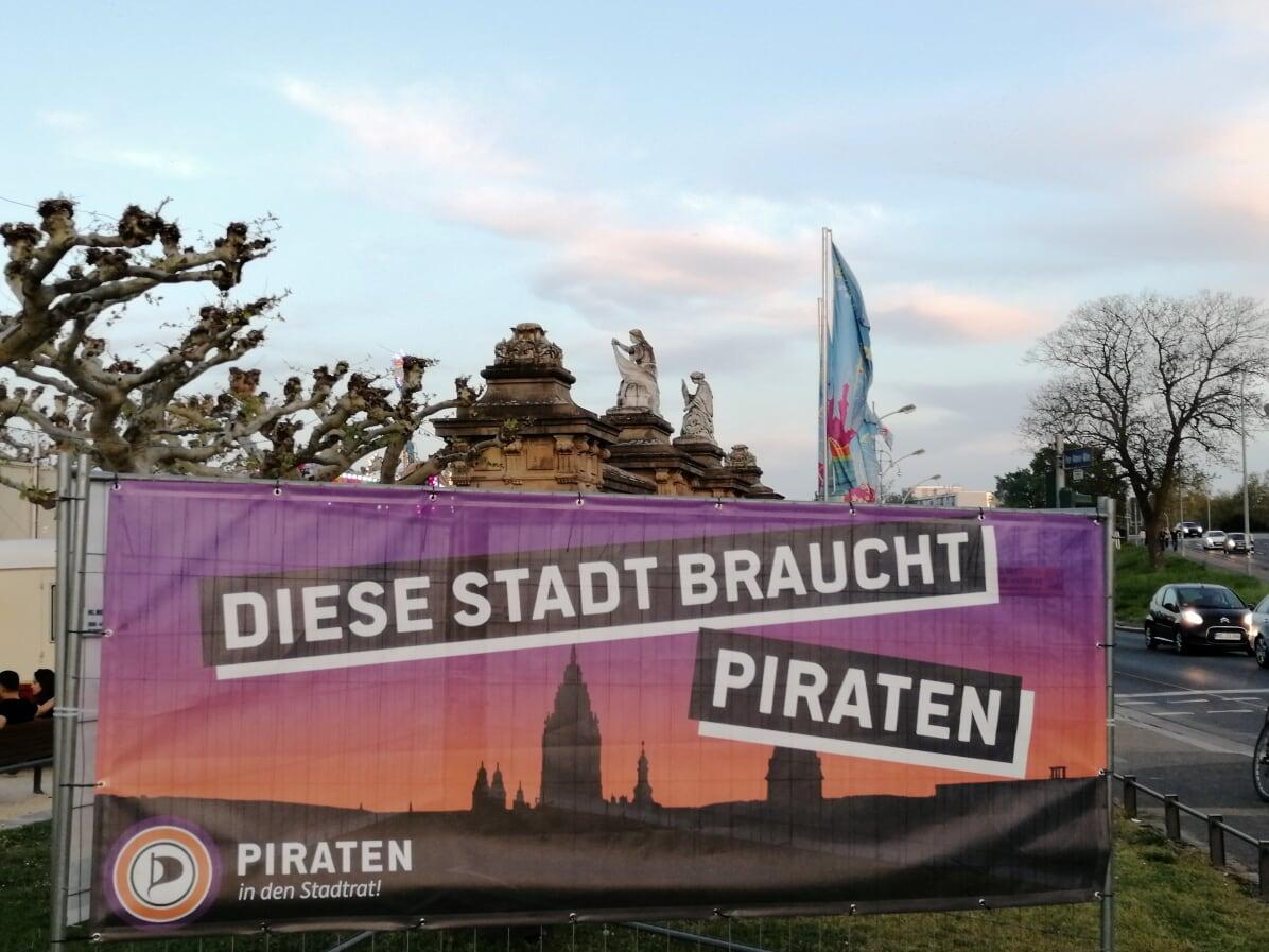 """Auf dem Bild ist ein Transparent mit der Aufschrift """"Diese Stadt braucht Piraten"""" zu sehen."""