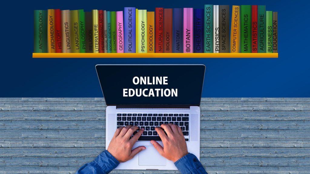 Notbook mit den Worten Online Education vor einem Bücherregal