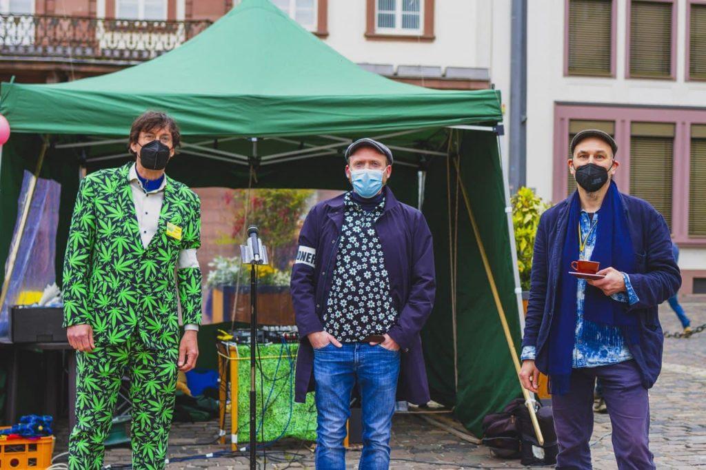 Organisatoren Christoph Lehner im Hanfanzug und andere Roland Hoffmann mit Kaffeetasse in der Hand vom Hanfverband Rhein Neckar zusammen mit Heinz Zell vor dem Microfon auf dem GMM